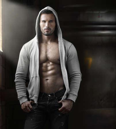 Jonge knappe macho man met open jas onthullende gespierde borst en buik in industriële garage met venster licht