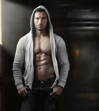 naked man: Young handsome macho man with open jacket revealing muscular chest and abs in industrial garage with window light