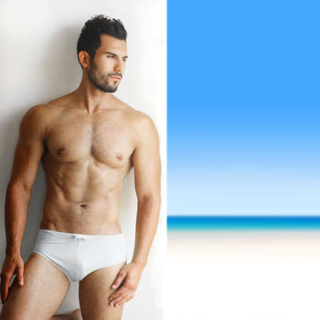 naked man: Sexy portrait of a very muscular shirtless male model in underwear against white wall in sensual pose with tropical paradise in background
