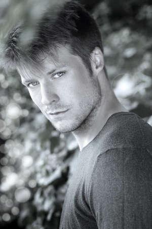 Fine art close-up zwart-wit portret van mooie jonge man draaien in de richting kijker