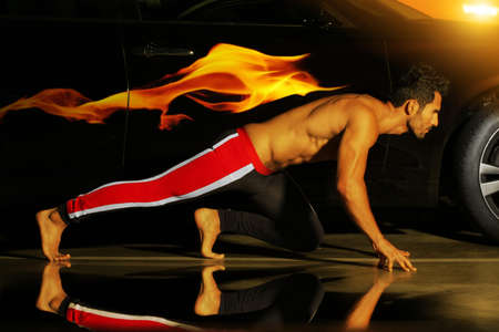 Concept photo of a young muscular athlete posed ready to run with car and flame behind him Stock Photo