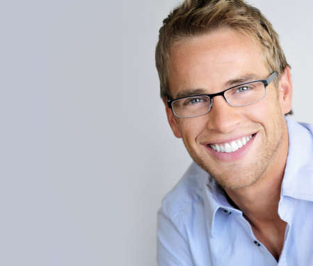 eyewear fashion: Young handsome man with great smile wearing fashion eyeglasses against neutral background
