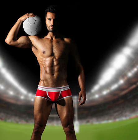 Sexy muscular man as soccer player in red underwear holding ball on field in crowded stadium