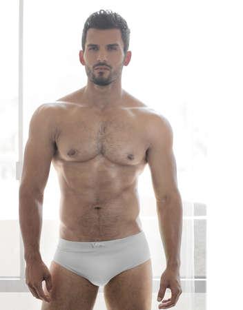 naked man: Muy sexy joven modelo masculino musculoso en ropa interior blanca delante de la ventana