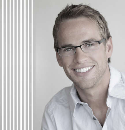 man  glasses: Young handsome man with great smile wearing fashion eyeglasses against neutral background with copy space
