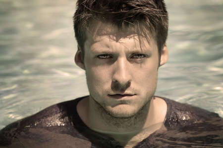 Stylized close-up portrait of young handsome male face in water, looking at camera