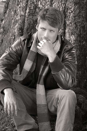 Classically dressed young male model outdoors in fall clothing with jacket and scarf photo