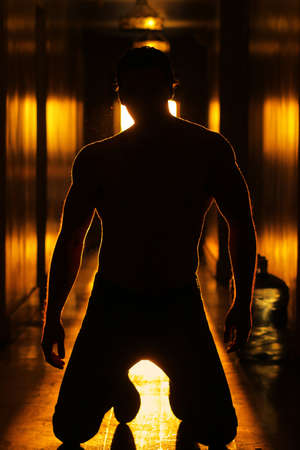 Silhouette of a sexy mysterious man with good body in glowing retro hallway