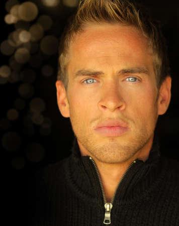 아름다운 푸른 눈을 가진 젊은 금발 남자의 상세한 초상화를 닫습니다