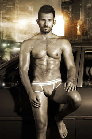 naked male body: Sexy portrait of a very muscular male model in underwear leaning against car in sensual pose in sepia tones with cool grunge city background