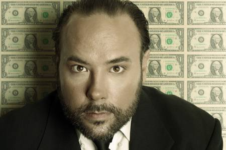 suggesting: Portrait of a serious businessman in suit against background of US dollar bills with overall green toning suggesting greed
