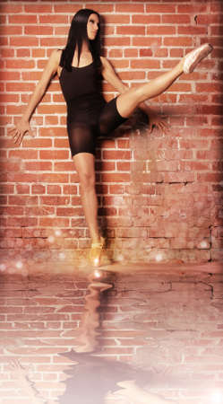 Young beautiful dancer in ballet pose with leg extended against brick wall background photo