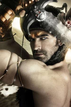 savaşçı: Kılıç ve kask ile eski savaşçı gibi seksi bir erkek modelin portresi