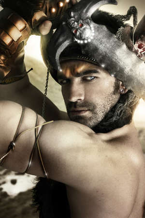 Portrait of a sexy male model as ancient warrior with sword and helmet photo