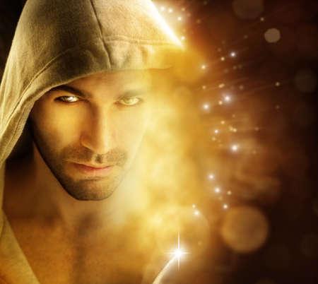 まばゆいばかりにフード付きの衣服でハンサムなヒーロー型男の幻想的な portriat 背景光の光線