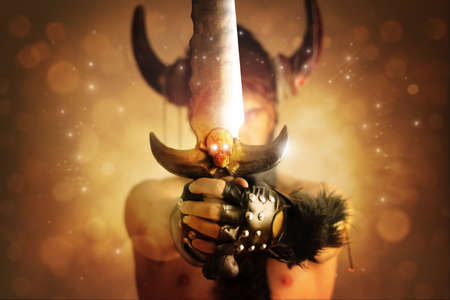 warrior: Fantastical portrait of a warrior with focus on powerful sword with skull against magical background of rays of light Stock Photo