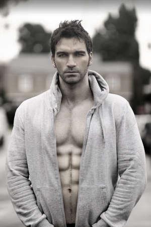 Sensueel humeurig portret van een fantastische man in jasje met een kap buiten Stockfoto