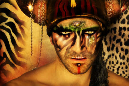 Fashion stylized concept portrait of a young man with tribal face painting and animal elements in front of a animal print background Banque d'images