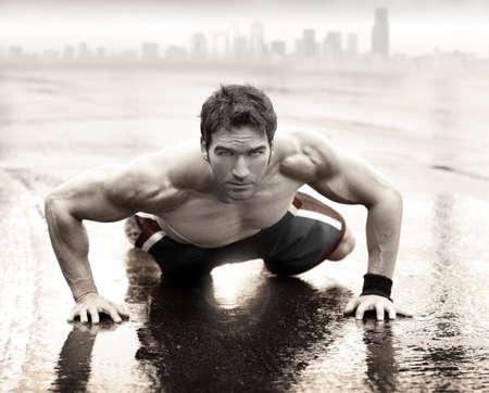 fitness training: Sexy fit gespierde man doen push-up op natte weg met skyline van de stad op de achtergrond