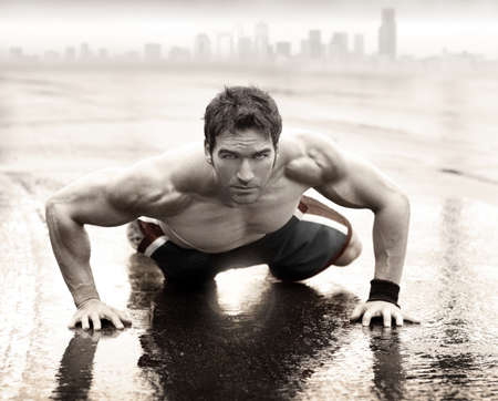 Sexy fit muscular man doing push-up on wet road with city skyline in the background Stockfoto