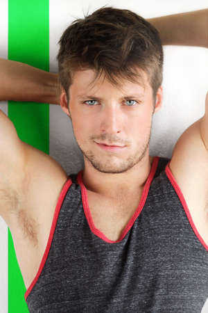 Young handsome male model with arms up in tank top against modern background with green stripe