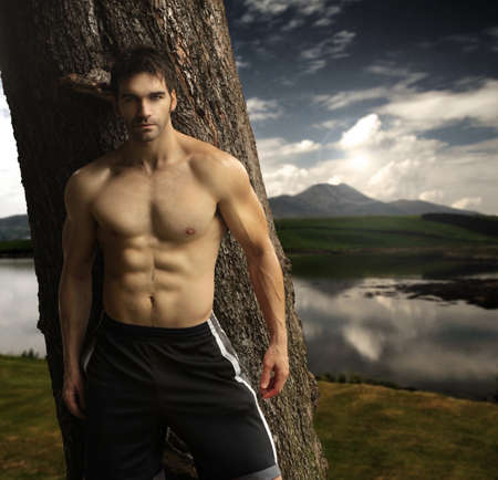 naked abs: Outdoor natural portrait of a gorgeous male fitness model  Stock Photo