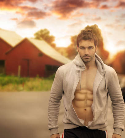 Beautiful male model with great body in romantic rustic outdoor setting with red barn in background and moody sky above Banque d'images
