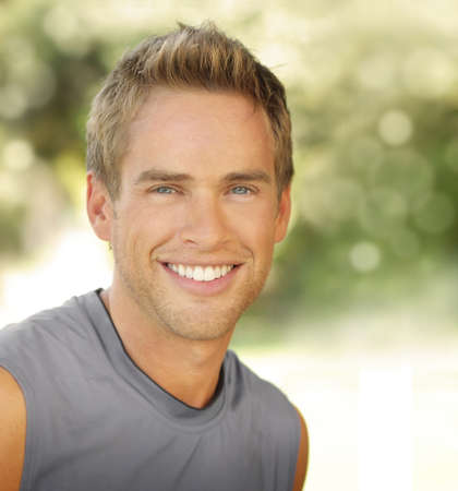 Satisfied smiling young male outdoors with copy space photo