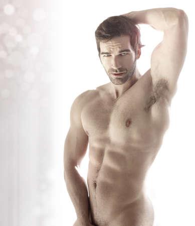 hombre desnudo: Muscular joven sexy hombre desnudo lindo contra fondo brillante abstracto moderno Foto de archivo