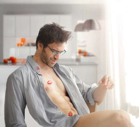 Portrait of sexy man at home with shirt open and lipstick kiss marks on his bare body and playful fun expression Stock Photo - 17383337