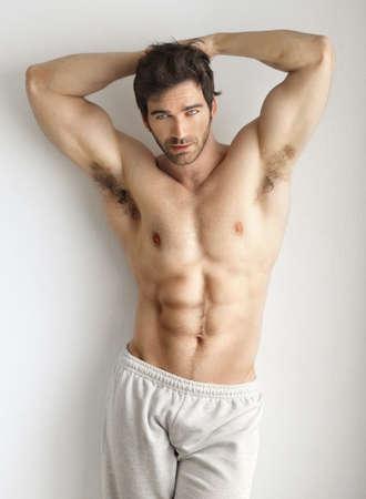 desnudo masculino: Sexy retrato de un modelo muy musculosos sin camisa masculina contra la pared blanca en pose sensual