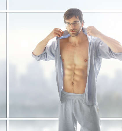 Sexy male model with hot  body with open shirt against modern background window Foto de archivo