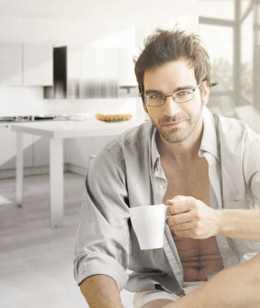 Interior portrait of a hot looking relaxed happy male model with a cup of morning coffee photo