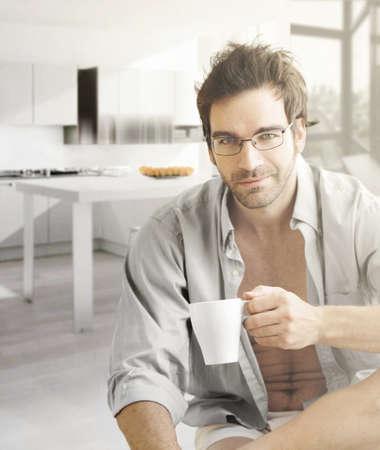 var�n: Retrato interior de un caliente buscando relajado modelo masculino feliz con una taza de caf� por la ma�ana
