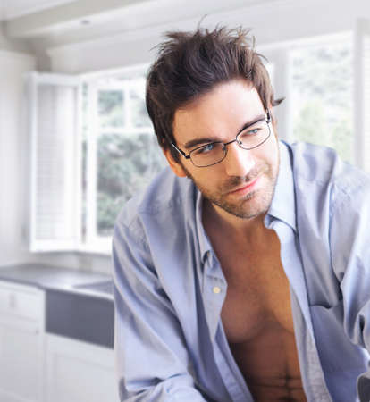 stubble: Young handsome man wearing fashion eyeglasses in bright modern interior Stock Photo