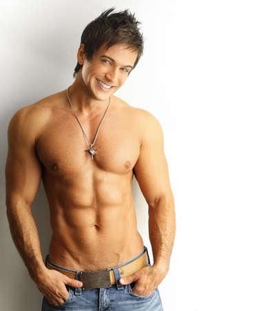 desnudo masculino: Sexy retrato de una joven modelo masculino musculoso con gran sonrisa feliz contra la pared blanca Foto de archivo