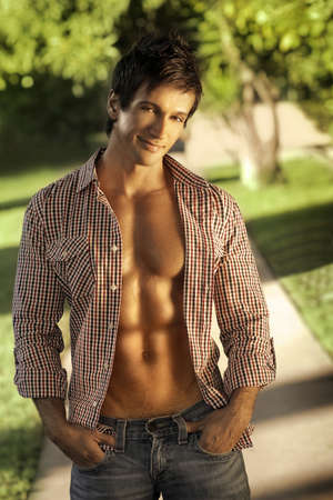masculine: Fashion portrait of a handosme man with open shirt and muscular abs outdoors