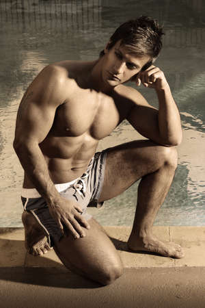 Sexy muscular male model posing with arm on knee thinking against vintage style setting and lots of shadow play photo