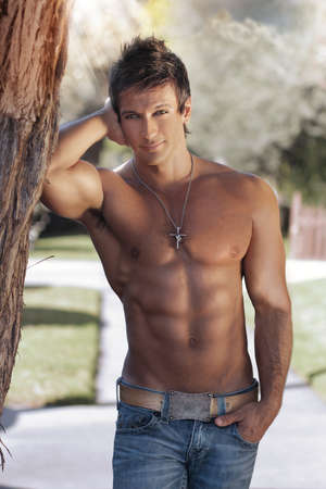 hombre sin camisa: Retrato de una bella joven musculoso apoyado contra un árbol en la naturaleza Foto de archivo