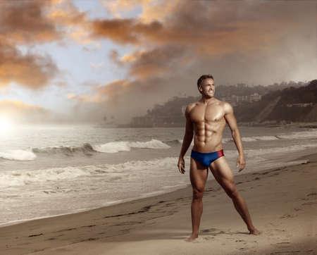 섹시한 백인 맞는 사람이 아름다운 하늘과 해변에서 포즈
