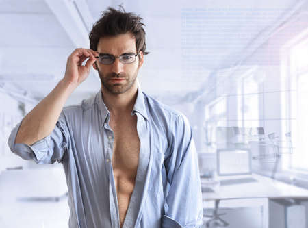 Sexy hunk male model with open shirt in modern business setting with blue toning  photo