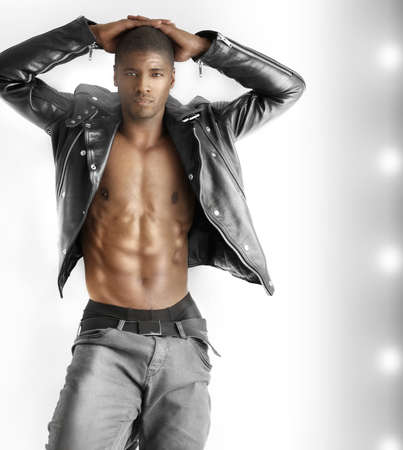 poses de modelos: Retrato de un apuesto joven modelo en forma masculina en ropa de moda contra el fondo moderno con copyspace