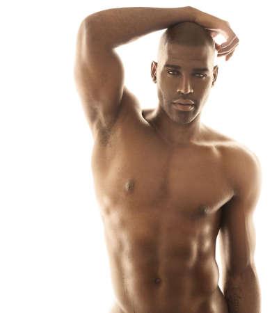 Fashion portrait sensuel d'un modèle d'ajustement mâle nu posant sur fond blanc lumineux