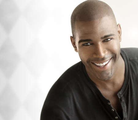 Portrait d'un jeune homme joyeux occasionnel souriant sur le fond blanc moderne avec copie espace