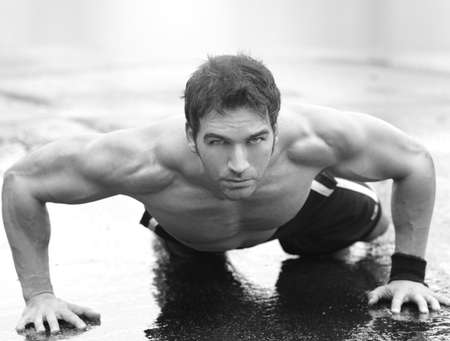 sweat: Inspirational portrait of a muscular fit man doing pushups on wet cement Stock Photo