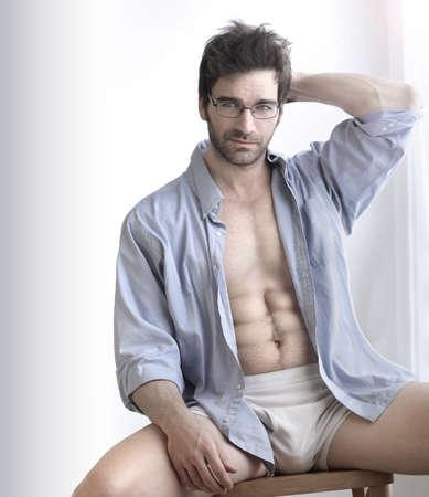 Ludique portrait d'un homme sexy buff beau en sous-vêtements et chemise d'affaires ouvert à l'expression sensuelle contre le blanc Banque d'images