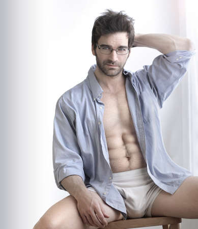 Playful sexy portrait of a handsome buff man in underwear and open business shirt with sensual expression against white photo