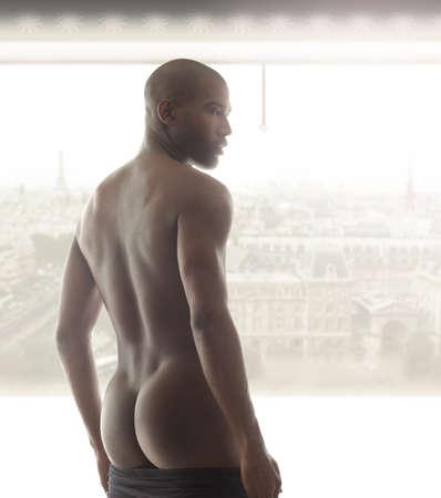 Portrait d'un beau modèle masculin par derrière contre la fenêtre lumineuse