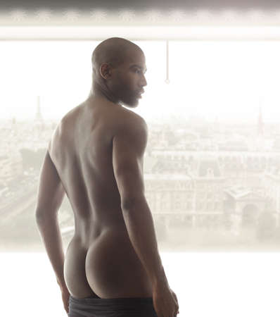Portrait of a beautiful male model from behind against bright window Stock Photo