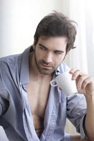 Portrait intérieur d'un Modèle mâle sexy détendue chaud avec une tasse de café du matin Banque d'images